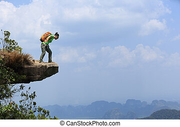 successful woman hiker enjoy the view at mountain peak cliff