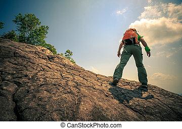 successful woman hiker hiking on mountain peak
