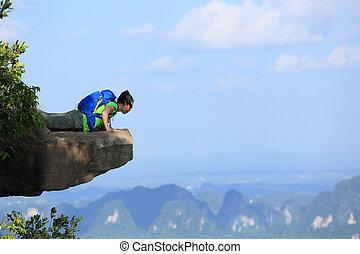 successful woman hiker looking down on mountain peak cliff