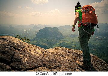 successful woman hiker mountain peak cliff