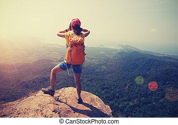 successful woman hiker stand on mountain peak cliff edge