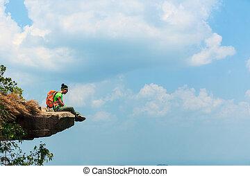 successful woman hiker thinking on mountain peak cliff