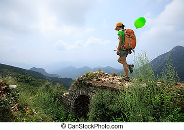 successful woman hiker walking on the top of mountain