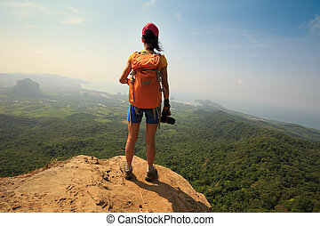successful woman photographer on mountain peak cliff