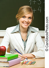 Portrait of young teacher checking copybook with books near by and looking at camera with smile