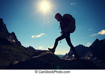 successful woman with backpack hiking in sunrise mountains