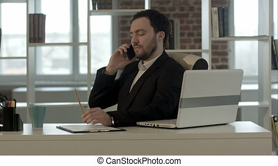 Successful young business man talking on cell phone at modern office