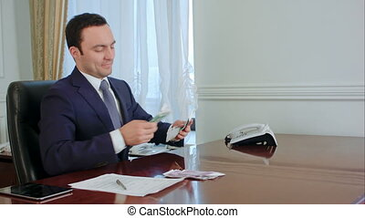 Successful young businessman counts euro bills speaking with colleague in the office. Professional shot in 4K resolution. 055. You can use it e.g. in your commercial video, business, officee, presentation, broadcast video.