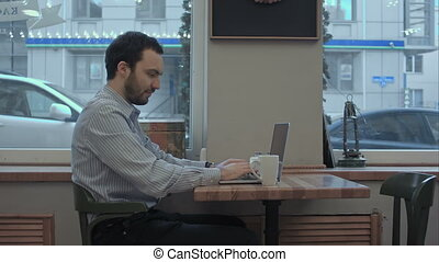 Successful young businessman is working on his laptop in cafe and drinking coffee