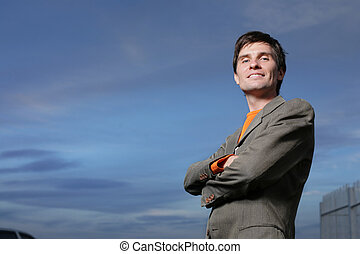 Successful young businessman over blue sky