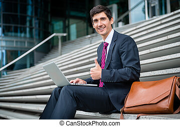 Successful young businessman showing thumb up outdoors