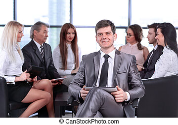 successful young businessman with clipboard on the background of business team