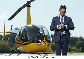 Successful young CEO waiting for a helicopter ride