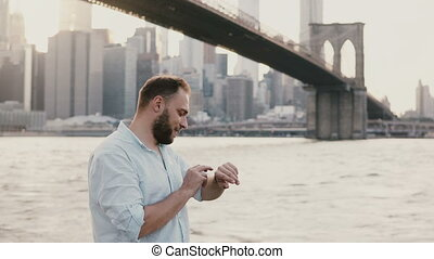 Successful young European businessman standing near river under Brooklyn Bridge, using his smart watch, walking away 4K.