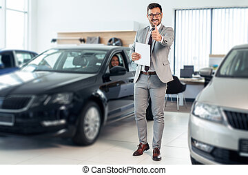 Successful young male working in car dealership