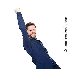 Successful young man smiling with arms raised