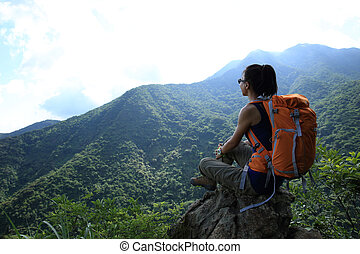 successful young woman hiker hiking on mountain peak