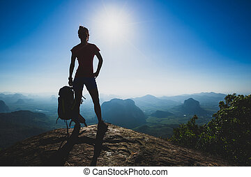 Successful young woman hiker stand on sunrise mountain peak cliff edge
