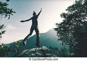 successful young woman jumping on cliff's edge