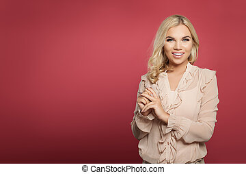 Successful young woman standing against pink wall background. Blonde girl smiling