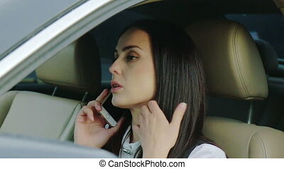 Successful young woman talking on a phone in her car