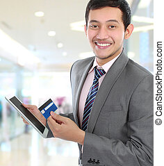 potrait of young business man hold a tab and credit card
