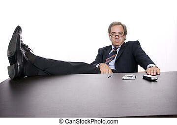 Successfull businessman relaxing over his desk, isolated in white background