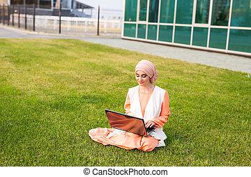 succesvolle , moslim, vrouw, en, laptop., arabier, businesswoman, vervelend, hijab, doorwerken, een, draagbare computer, in, de, park.
