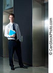 sucedido, homem negócios, escritório, elevador, sorrindo