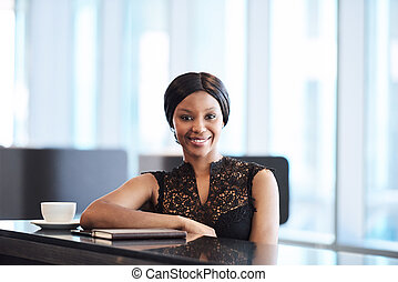 Sucessful black businesswoman looking into camera while...
