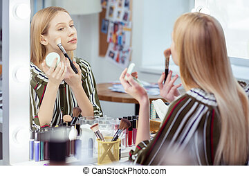 Nice attractive woman looking at her reflection