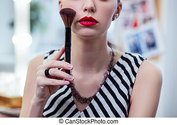 Nice young woman holding her makeup brush