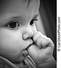 A baby girl sucking her thumb