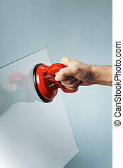 Suction Cup - Man lifting a sheet of glass using a vacuum...