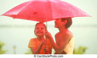 Boy and girl hiding under umbrella from a sudden summer rain