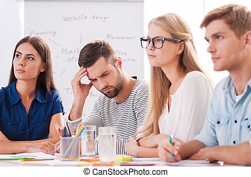 Suffering from awful headache. Depressed young man touching head with hand while sitting at the table together with his colleagues