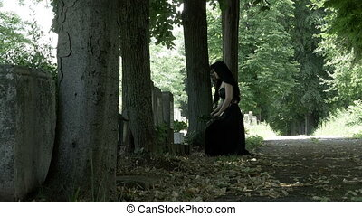 Suffering mourning woman in funeral dress on her knees at...