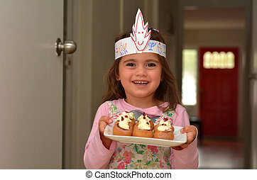 Jewish child (girl age 05) carries a plate full with mini Sufganiyot / doughnuts filled with strawberry jelly on Hanukkah Jewish Holiday.