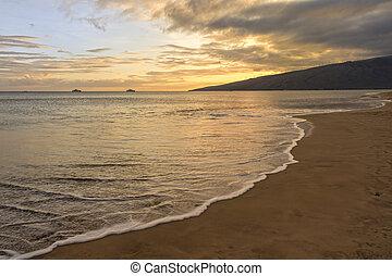 Sugar beach Kihei Maui Hawaii at sunset as a wave washes...