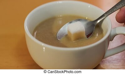 Sugar cube absorbing coffee throug capillary action, slow...