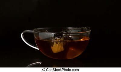 Sugar cube falling into cup of tea - Sugar cube falling into...