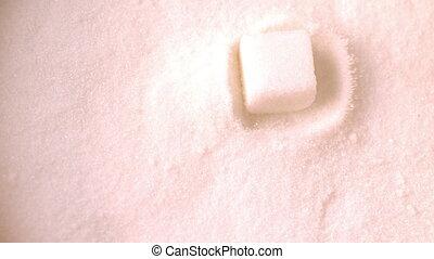 Sugar cube falling into pile