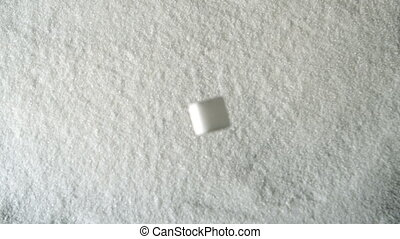 Sugar cube falling into pile of sug