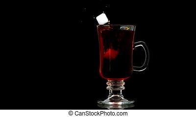 Sugar cube falling into tea in a glass