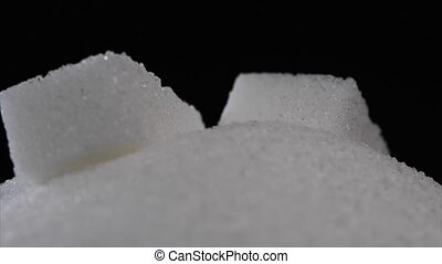 Sugar cube falling on pile of sugar on black background