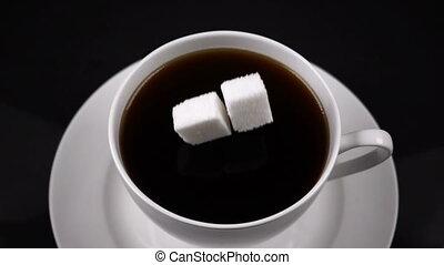 sugar cubes dropped into coffee creating splash