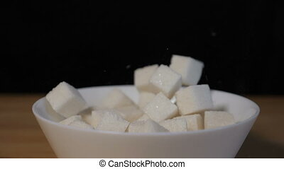 Sugar cubes falling into bowl