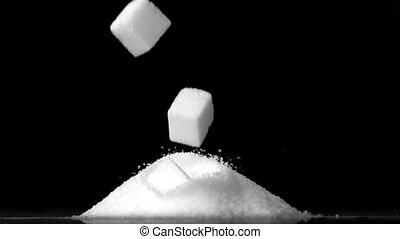 Sugar cubes falling into pile of sugar on black background in slow motion
