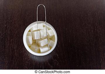 Sugar cubes in sugar bowl and sugar tongs