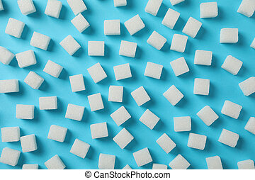 Sugar cubes on blue background, top view